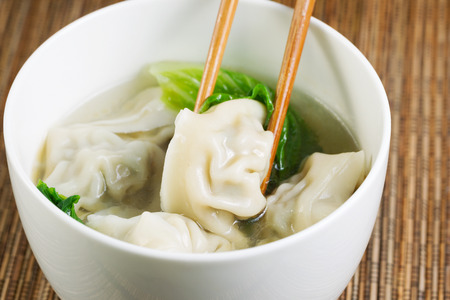Close up horizontal top view photo of freshly made wonton with chopsticks picking up single piece