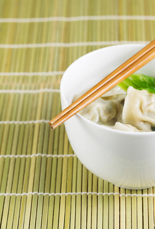 Close up vertical photo of freshly made wonton with chopsticks on top of white bowl  photo