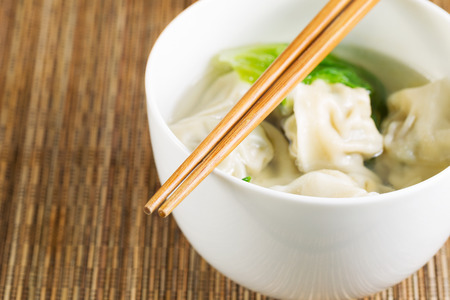 Extreme close up horizontal photo of freshly made wonton with chopsticks on top of white bowl  Stock Photo