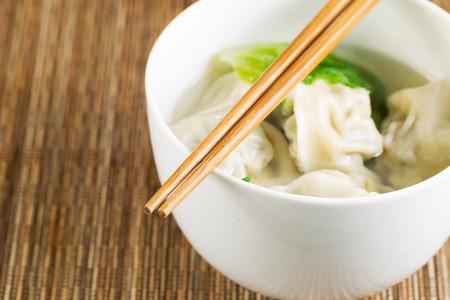 Extreme close up horizontal photo of freshly made wonton with chopsticks on top of white bowl Stock Photo - 26542647