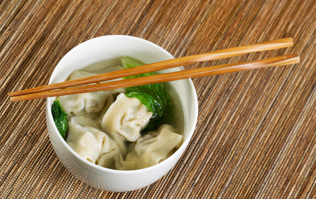 Close up horizontal top view photo of freshly made wonton with chopsticks on top of white bowl  photo