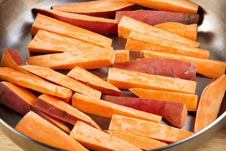 Horizontal photo of freshly cut Yams in stainless steel frying pan ready for cooking into French fries