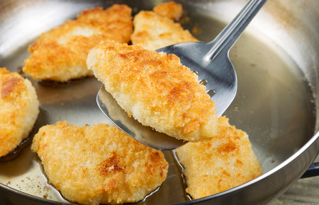 Horizontal photo of golden breaded coated fish being fried in stainless steel frying pan with focus on single piece with spatula underneath