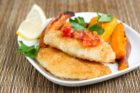 potato cod: Closeup horizontal of golden crisp fried cod fish with salsa sauce on top with Yam Fries in background  Stock Photo