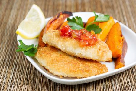 pescado frito: Horizontal Primer plano de crujiente bacalao frito dorado con salsa de salsa en la parte superior con patatas fritas de ñame en el fondo