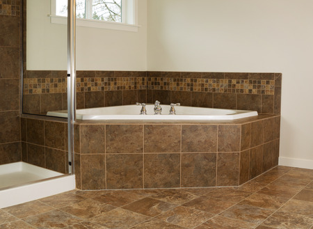 Horizontal photo of soaking tub in master bathroom with partial shower and windows  photo