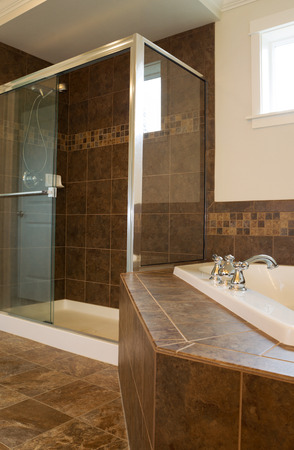 bathroom tile: Vertical photo of walk in glass shower in master bathroom with partial soaking tub and window in background  Stock Photo