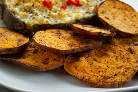 Horizontal closeup photo of baked yam slices and fish on white plate