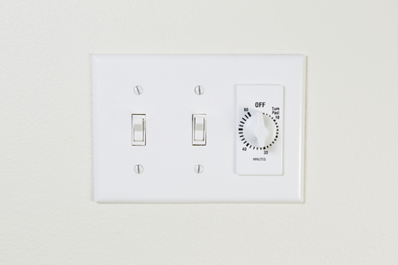 Horizontal photo of bathroom fan and light switches with timer on wall photo