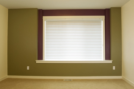Horizontal photo of interior residential home accent wall painted green with large window and shade in background   photo