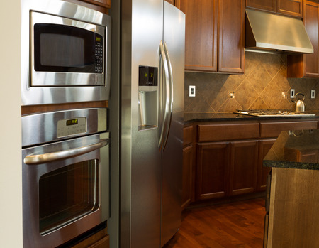 stove: Closeup photo of a stainless steel appliances in modern residential kitchen with stone counter tops and cherry wood cabinets with hardwood floors
