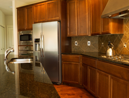 Closeup photo of a walkway behind Kitchen Island with stainless steel appliances, gas stove, stone counter tops and cherry wood cabinets with hardwood floors  photo