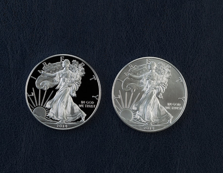 american silver eagle: Closeup photo of a proof and uncirculated American Silver Eagle Dollar Coins side by side on dark blue vinyl holder