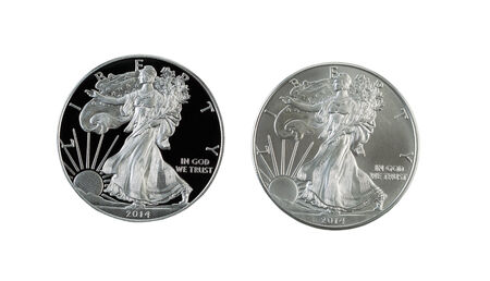 Closeup photo of a proof and uncirculated American Silver Eagle Dollar Coins side by side isolated on white  photo