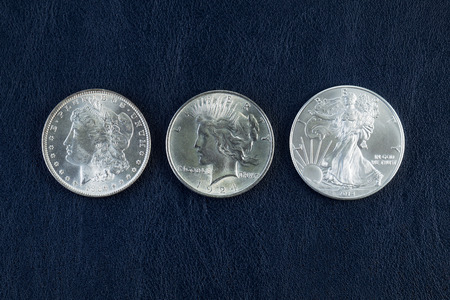 american silver eagle: Closeup horizontal photo of a Morgan, Peace and American Silver Eagle Dollars on Blue Vinyl Holder