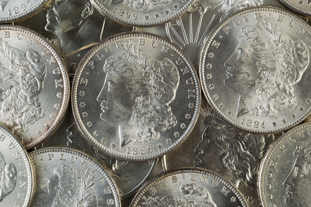 about us: Closeup horizontal photo of several United States Silver Dollars, obverse side up, piled up
