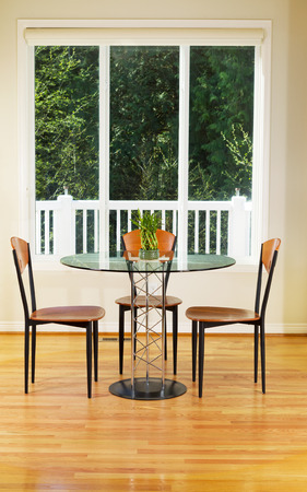 Vertical photo of small dining room with red oak floors, glass table, wooden chairs, bamboo plant and large windows with evergreen trees in background  photo