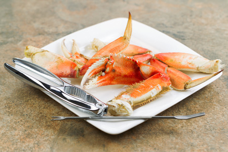 Horizontal photo of freshly cooked Dungeness crab legs, focus on large claw in center, on white plate with stainless crab crackers and stone counter top underneath   photo