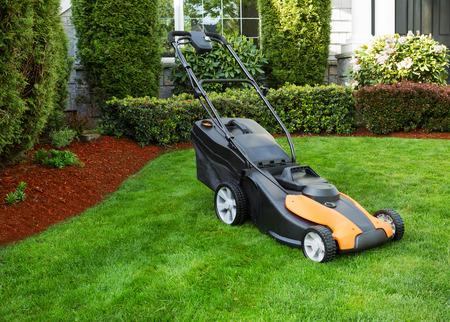elektrische grasmaaier op vers gesneden pluche groen gras met huis en bloemperken in de achtergrond