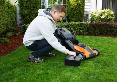 volwassen man brengen in de batterij in elektrische grasmaaier op vers gesneden pluche groen gras met huis op de achtergrond