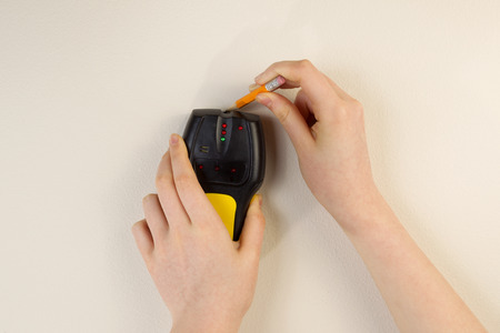 Photo of female hands holding using stud finder and pencil against interior home white wall Stock Photo