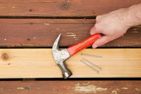 porches: Horizontal photo of male hand picking up old hammer to install new cedar wood board into aging deck