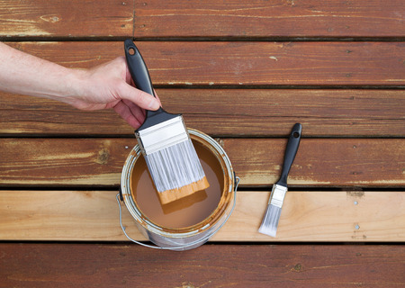 stain: Horizontal photo of male hand dipping paint brush into a can of wood stain with single small brush lying on a single new cedar wooden board next to fading wood on outdoor deck