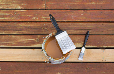 wood stain: Horizontal photo of large nylon paint brush on top of wood stain can with small paint brush lying on a single new cedar wooden board next to fading wood on outdoor deck