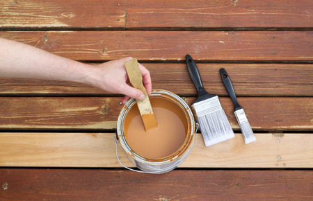 stain: Horizontal photo of male hand stirring wood stain in can with stir stick with two paint brushes lying on a single new cedar wooden board next to fading wood on outdoor deck