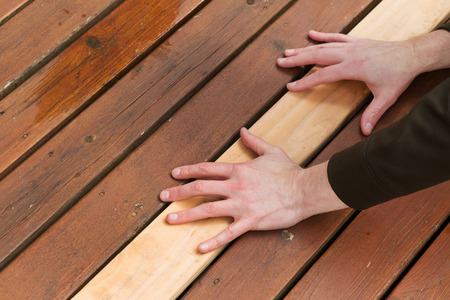old wood floor: Horizontal photo of male hands putting in a single new cedar wooden board next to fading wood on outdoor deck  Stock Photo