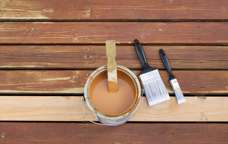 stain: Horizontal photo of an open can of wood stain with two paint brushes lying on a single new cedar wooden board next to fading wood on outdoor deck  Stock Photo
