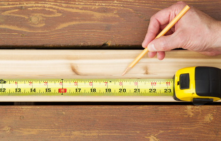 fading: Horizontal photo of hand holding pencil next to tape measure on top of new cedar wood board next to fading wood on outdoor wooden deck