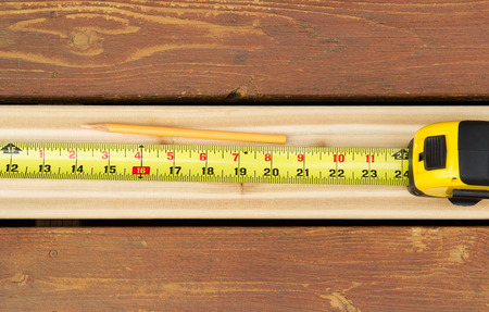 lumber industry: Horizontal photo of tape measure and pencil on top of new cedar wood board next to fading wood on outdoor wooden deck