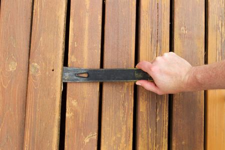 pry: Horizontal photo of hand with pry bar lifting up old cedar wood board on outdoor wooden deck