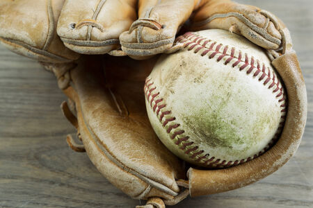 scuffed: Closeup horizontal photo old dirty baseball inside of heavily used glove on rustic wood