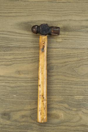 peen: Vertical photo of an old ball peen hammer on aged wood