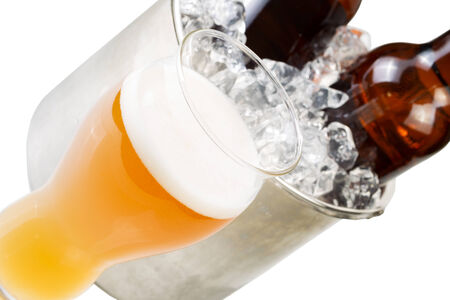 bottled beer: Closeup angled horizontal photo of freshly poured beer in large glass and bottled beer in stainless steel bucket filled with ice isolated on white