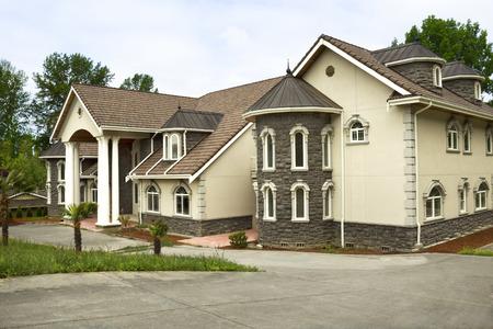 Horizontale foto van de gloednieuwe aangepaste woning gebouwd met palmbomen aan de voorzijde en grote voor rijden met bomen en deels blauwe hemel op achtergrond