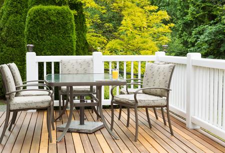 Close-up horizontale foto van tuinmeubilair op open ceder patio met seizoensgebonden bomen in volle bloei in de achtergrond