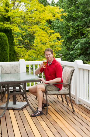 brew beer: Vertical photo of mature man looking forward and smiling while holding his glass of beer at the table on open cedar patio with seasonal trees in full bloom in background