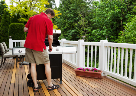 Closeup horizontal photo of mature man working on BBQ grill on open cedar patio with seasonal trees in full bloom in background  photo