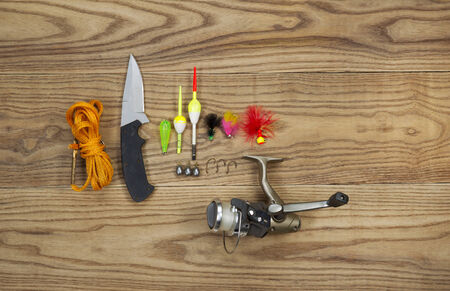 sinkers: Horizontal top view photo of fishing lures, bobbers, sinkers, hooks, knife, reel and stringer on faded wood Stock Photo