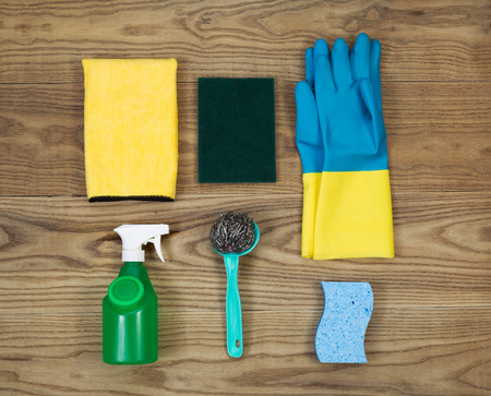 disinfecting: Overhead view of house cleaning materials placed on rustic wood.  Items include sponge, rubber gloves, stainless steel pad, spray bottle, microfiber rag, and scrub pad.