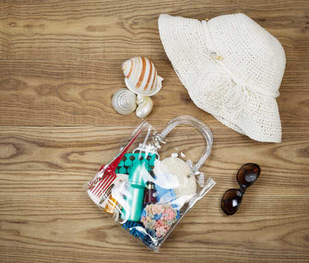 sun screen: Overhead view of outdoor kit placed on rustic wooden boards.  Items include clear plastic bag, comb, sun screen, hair clips, sea shells, sun glasses and white hat.