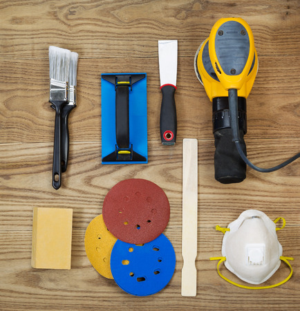 sanding block: Overhead view of sanding and painting equipment positioned on rustic wooden boards.  Items include electric sander, mask, stir stick, sand paper, scrapper, sanding block, and brushes.  Stock Photo