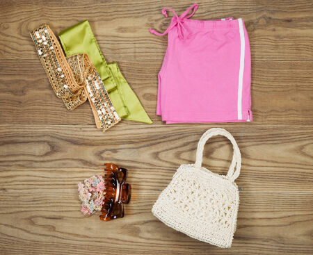 top clothing: Overhead view of summer clothing and accessories placed on rustic wooden boards.  Items include cloth purse, hair clips, elastics, and waist with head bands.