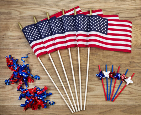 Overhead view of United States of America flags, ribbons and pinwheels positioned on rustic wooden boards.   photo