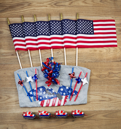 Overhead view of United States of America flags, ribbons, t-shirt, fire cracker, dog tag and pinwheels positioned on rustic wooden boards.   photo