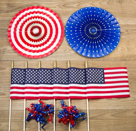 Overhead view of six United States of America flags, ribbons and large pinwheels positioned on rustic wooden boards.   photo