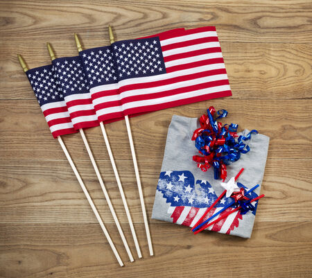 Overhead view of United States of America flags, ribbons, t-shirt and pinwheels positioned on rustic wooden boards photo